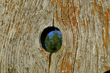An old weathered  corral fence board provides a perfect knot hole Stock Photo