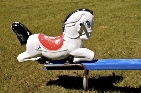 totter: An old plastic horse serves as a seat on the end of a vintage teeter totter