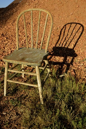 windsor: An old Windsor chair throws its shadow against a pile of scoria Stock Photo