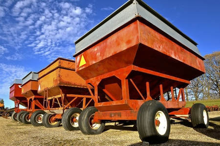 Row of colorful gravity boxes for self unloading of small grain. Stock Photo