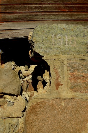 foundation cracks: An old foundation with cracks, fissures,  and holes from 1910 is crumbling and deteriorating. Stock Photo