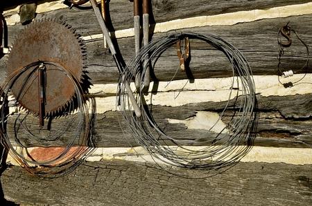 De muur van een oude blokhut is versierd met rollen draadgereedschap en een groot cirkelzaagblad.