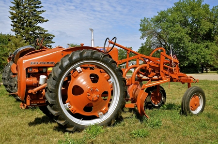 MEDINA, NORTH DAKOTA, July 1, 2016:  TheAllis Chalmers tractor with an attached grader blade is a product of a  U.S. manufacturer of machinery for various industries includung agricultural equipment, construction, power generation, and power transmission. Editorial