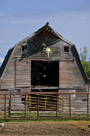 haymow: Metal corral barriers are placed in front of a rickety old wood hip roofed barn.