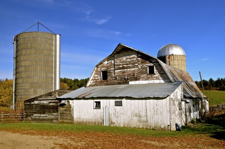 A deserted dairy operation with cement silos barn, and milking parlor Stock Photo