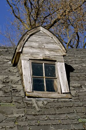 Dormer of an old decaying roof needing shingles 版權商用圖片