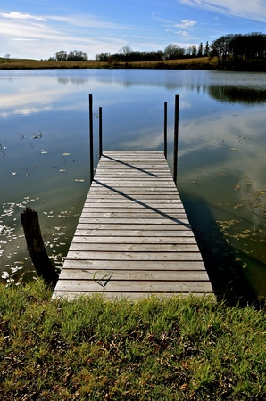 Dock leads into lake water on an early autumn morning Stock Photo