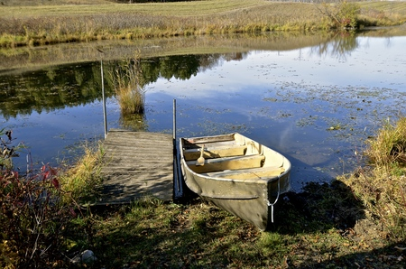 Surrounded by the autumn doors, a duck boat pulled ashore is along a dock in a small body of water