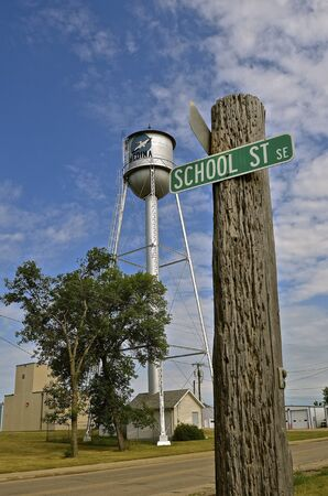 Street signs of the city of Medina, North Dakota are attached to an old telephone post Redakční