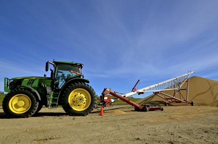 BATTLE LAKE, MINNESOTA, Oct 21, 2016:  The tractor operating a tube elevator is is a product of John Deere Co, an American corporation that manufactures agricultural, construction, forestry machinery, diesel engines, and drivetrains.