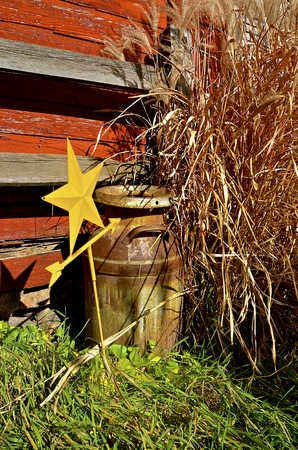 Milk can, long autumn grass, and decorative star by an old red barn