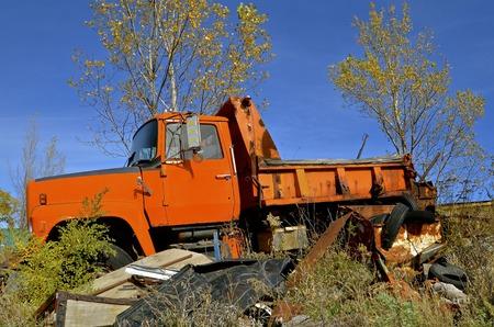 metalschrott: Eine orange bemalt Kreis dump und Sand LKW wird auf dem Schrottplatz für Altmetall und Bergungs links.