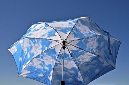An opened umbrella with a blue sky and cloud pattern blends into the blue outdoor sky