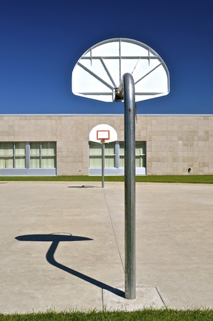 The shadow of a basketball apparatus is cast on the concrete of a an outdoor court adjacent to a school building