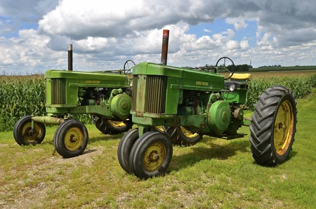 ULEN, MINNESOTA, July 27, 2016: The two old 70 John Deere tractors are products of John Deere Co, an American corporation that manufactures agricultural, construction, forestry machinery, diesel engines, and drivetrains.