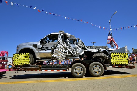 MANDAN, NORTH DAKOTA, July 3, 2016: The 4th of July Rodeo Days 3 day celebration includes the rodeo, Art in the Park, and downtown parade where a wrecked Sheriffs truck is displayed from vehicles not Moving Over to the left lane.
