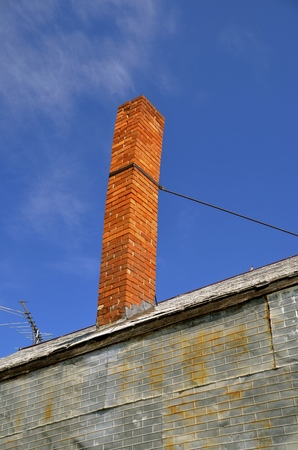 tall chimney: A tall old leaning chimney on an dilapidated metal building is reinforced with a metal strap.