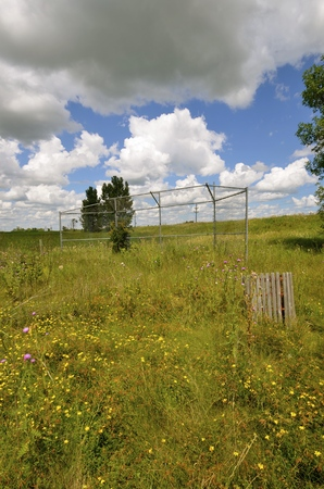 backstop: A former rural baseball is forgotten, neglected with only the backstop and garbage receptacle as former evidence of the athletic field.
