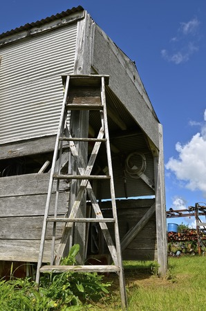 acquaint: A rickety old wood step ladder leans against acquaint storage shed in a junkyard Stock Photo