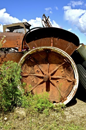 A very old rusty tractor and a real fender is missing a tire on the rim in a salvage junkyard