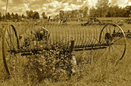 An old rusty dump rake is left in the weds and long grass of a salvage and junkyard of a field(sepia)