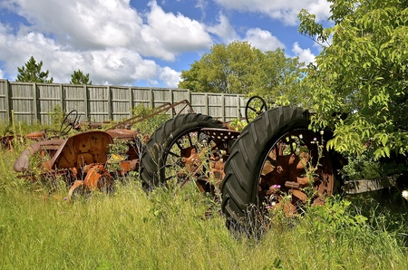 Old tractors are left in the bushes and weeds to be used for salvage and scrap metal. Stock Photo