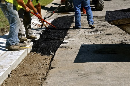 Crew workers spread asphalt with rakes and shovels between the curb and road