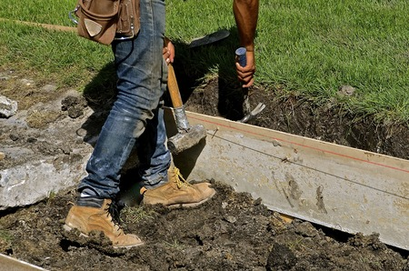 A worker in boots stands in the mud while building forms to keep wet concrete in place on curb and street construction