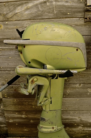 oldie: An old vintage green boat motor used for fishing and trolling leans again a weathered wooden fence