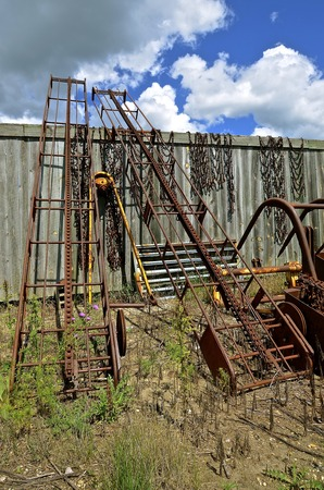 Several old rusty bale carriers for transporting the baled hay to higher levels lean against an old weathered wood fence Stock Photo