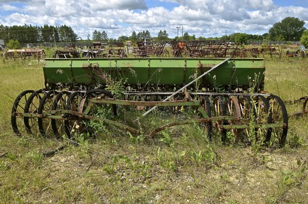 An old green vintage grain seed drill left in a salvage and junkyard