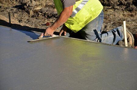 Construction worker troweling wet concrete on a sidewalk project