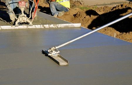 Stierenvliegtuig dat door bouwvakkers wordt gebruikt om nat betonstoepniveau te effenen en glad te maken Stockfoto - 74032137