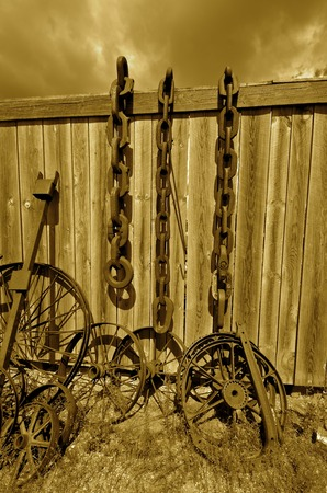 corrosion: (sepia)Old steel wheels and log chains lean against a wood fence in a salvage and junkyard