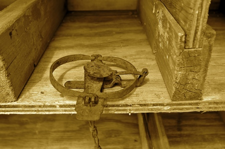 sprung: (sepia)An old gopher and rodent jump trap is set and ready for usage.