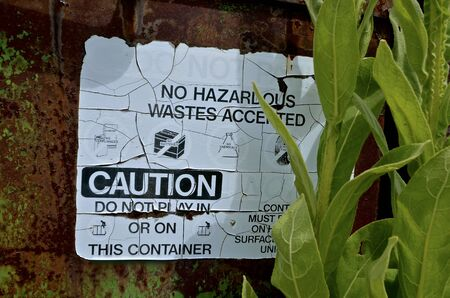 A retro warning sign of hazardous materials is left in an old rusty metal container