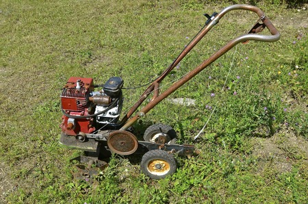 An old rusty garden tiller is ready for usage or to be sent to the junkyard for salvage, parts, or scrap metal