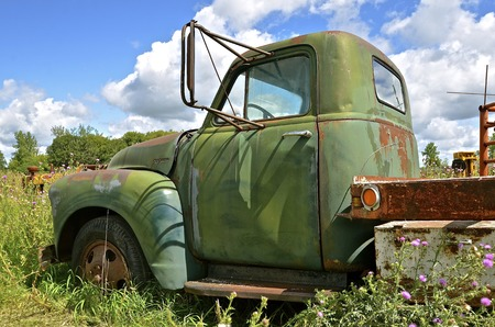 An old full ton pickup with a flat bed and extended mirrors is left in the wed patch.