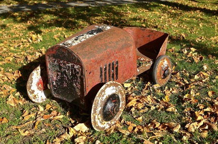 rusty car: Old rusty kids go cart, car, or pedal car parked in the autumn leaves Stock Photo