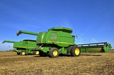 combines: SHELDON, NORTH DAKOTA, September 29, 2016 : The green self propelled combines in the autumn residue of a soybean field are products of John Deere Co, an American corporation that manufactures agricultural, construction, forestry machinery, diesel engines,