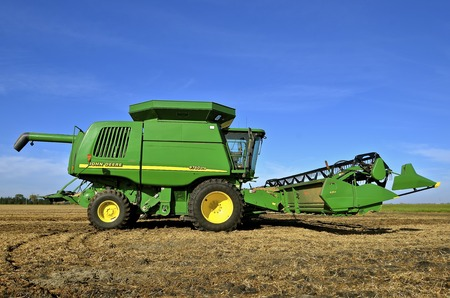 SHELDON, NORTH DAKOTA, September 29, 2016 : The green self propelled combine in the autumn residue of a soybean field is a product of John Deere Co, an American corporation that manufactures agricultural, construction, forestry machinery, diesel engines,