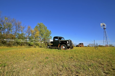 jalopy: And old junker pickup with spray booms and barrel are in a pasture with a water tower and pump.