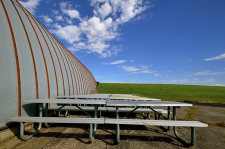Heavy duty metal picnic tables are stored next to a steel quonset building.