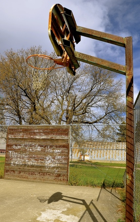 scribbling: A basketball backboard, hoop, and net in an outdoor court finds a wall with scribbling and words. Stock Photo
