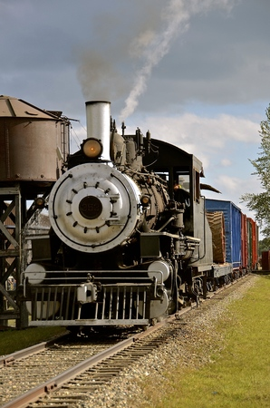 An old steam locomotive pulling freight train cars passes by a water tank