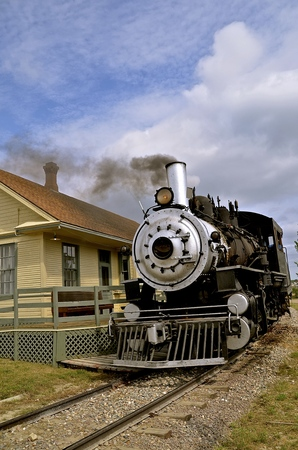 An old steam locomotive pulling freight train cars passes by a depot.