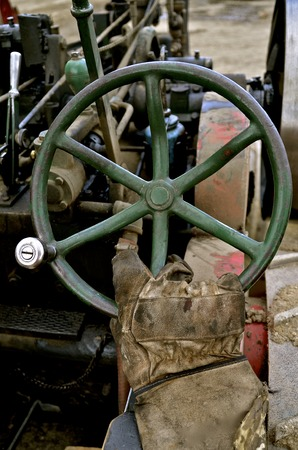 operates: A gloved hand operates the steering wheel of a very old steam driven tractor