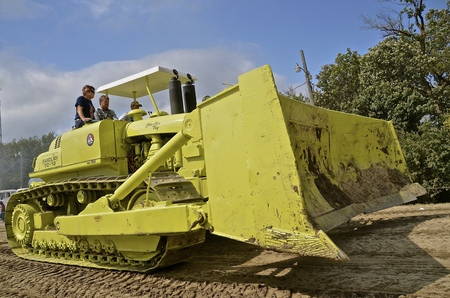 ROLLAG, MINNESOTA, Sept 2, 2016: Two unidentified men operate an old restored Euclid TC-12 bulldozer in a parade at the West Central Steam Threshers Reunion in Rollag, MN attended by 1000s held annually on Labor Day weekend.