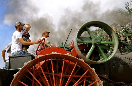 ROLLAG, MINNESOTA, Sept 2, 2016: Two unidentified men and a child operate an old restored steam engine in a parade at the West Central Steam Threshers Reunion in Rollag, MN attended by 1000s held annually on Labor Day weekend. Editorial