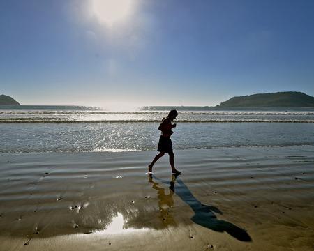 Un coureur silhouetté non identifié coule le long de la plage de sable à côté de l'océan. Banque d'images - 72721512
